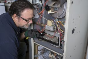 technician-performing-maintenance-on-furnace